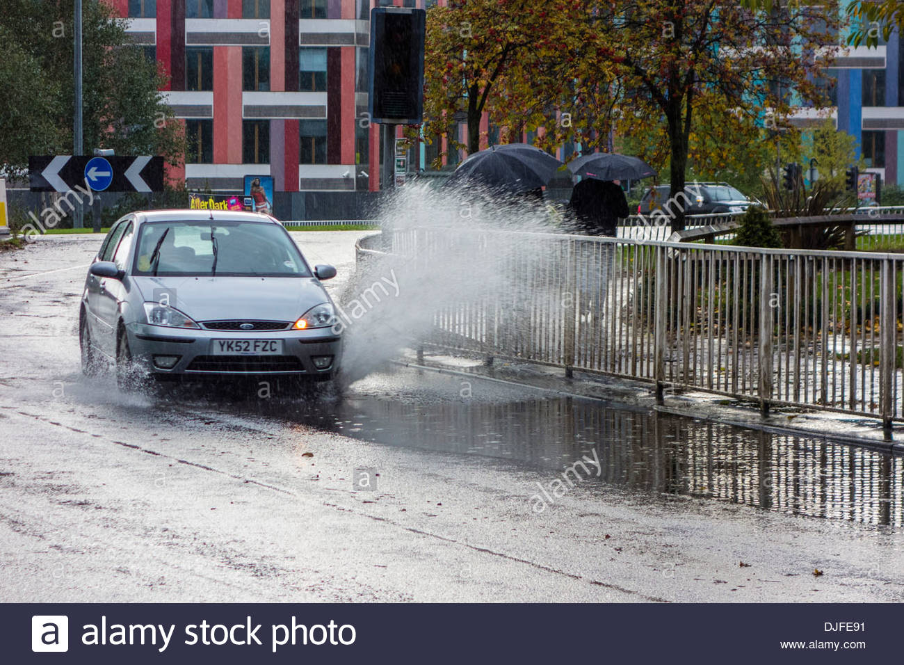 Cars rounding a bend in Sheffield hit a large puddle of water causing spray and splash - Stock Image