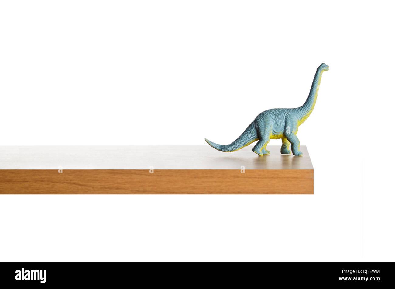 Dinosaur figurine placed on a ledge - Stock Image