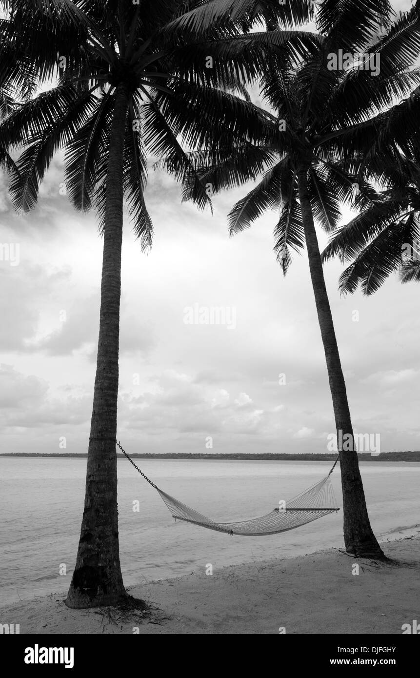 Landscape of hammock hanged between two coconut trees in Aitutaki Lagoon Cook Islands.(BW) - Stock Image
