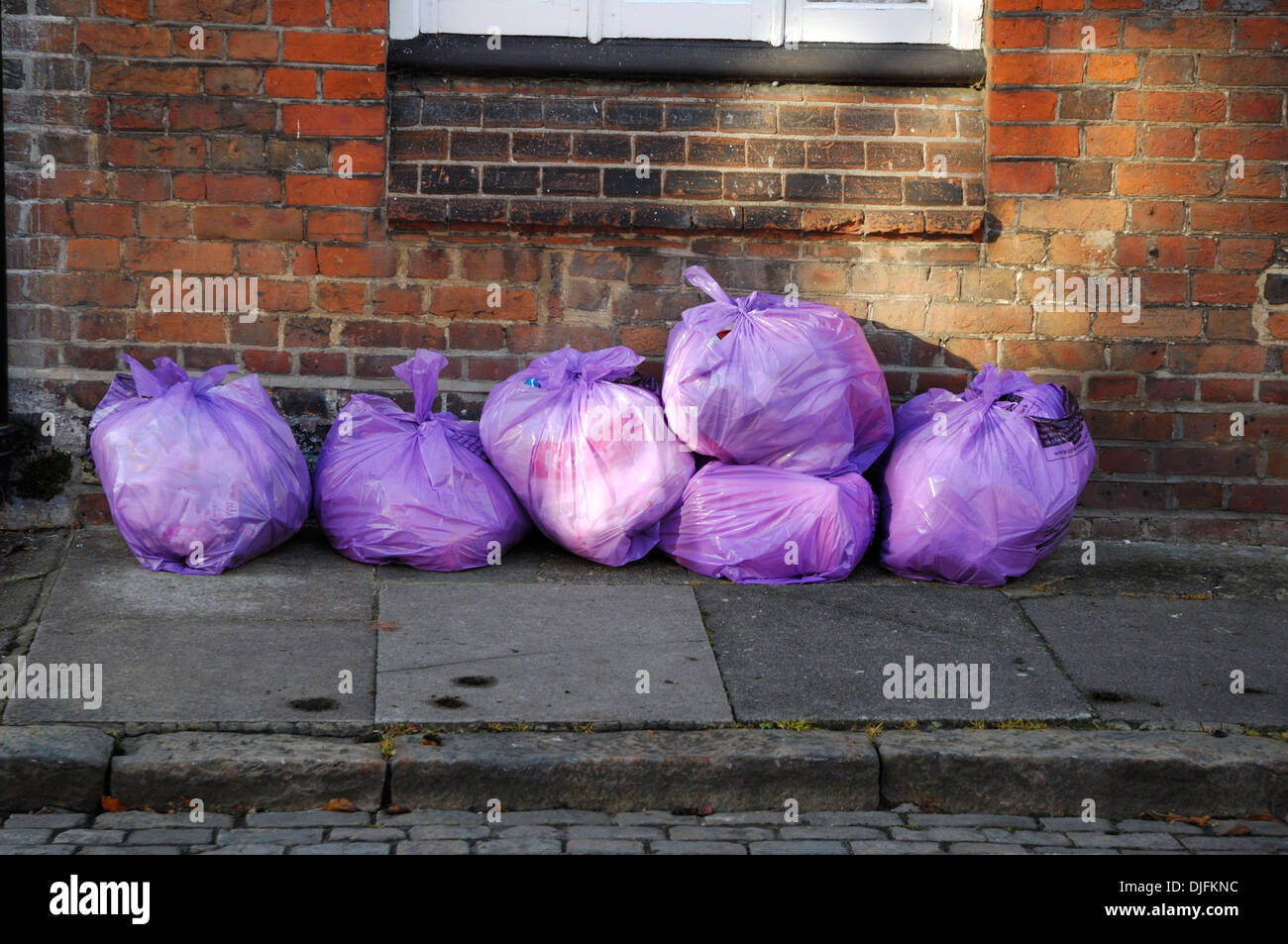 Rubbish bags left on pavement - Stock Image