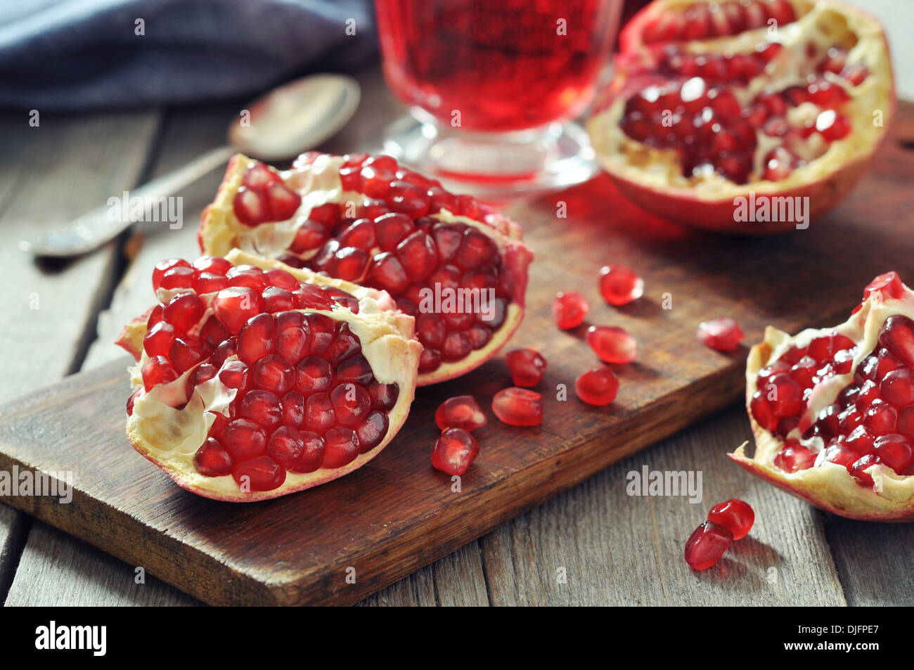 Ripe pomegranate fruit and glass of juice on wooden background Stock Photo
