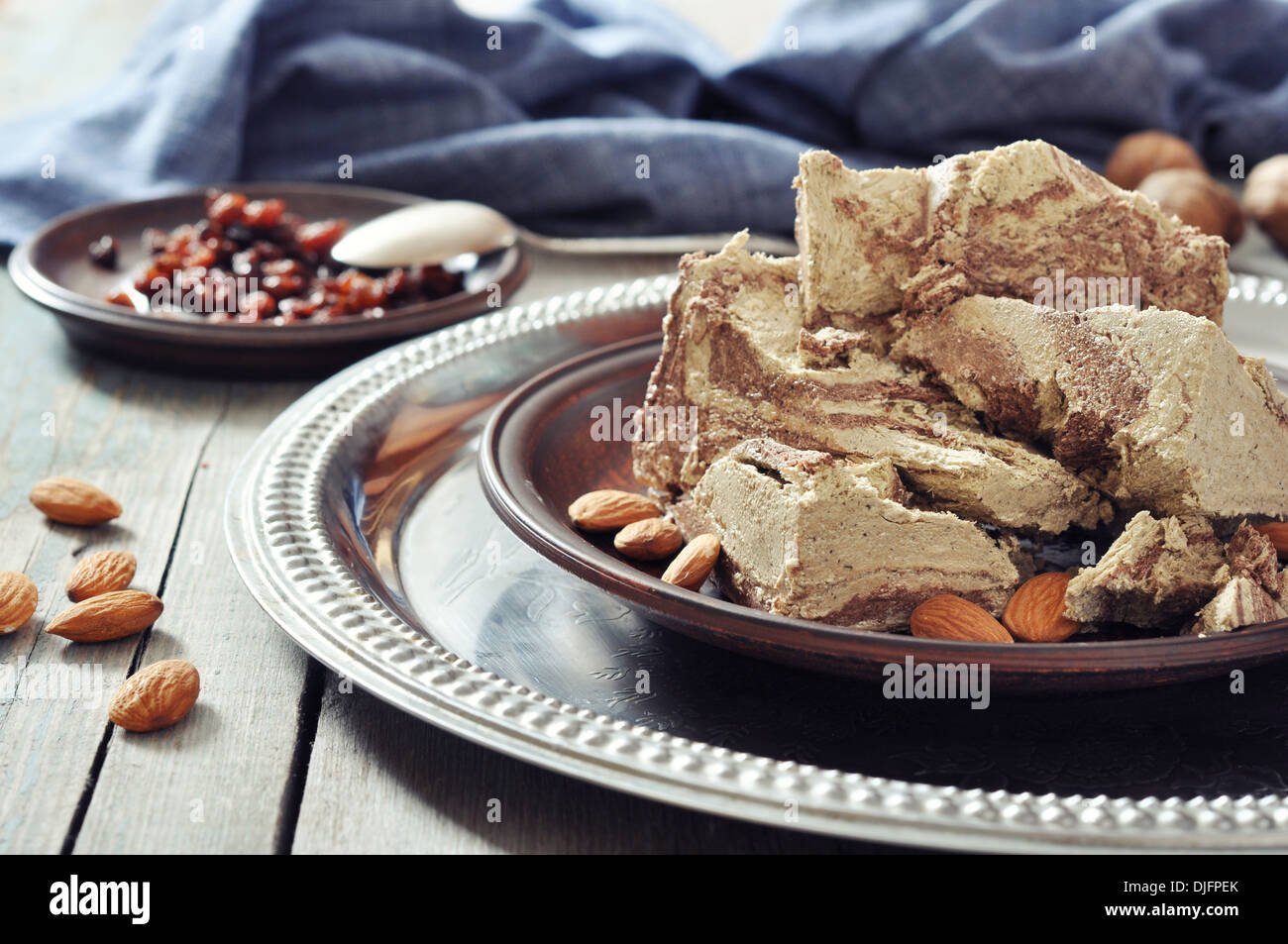 Halva with almonds and raisins on plate closeup - Stock Image