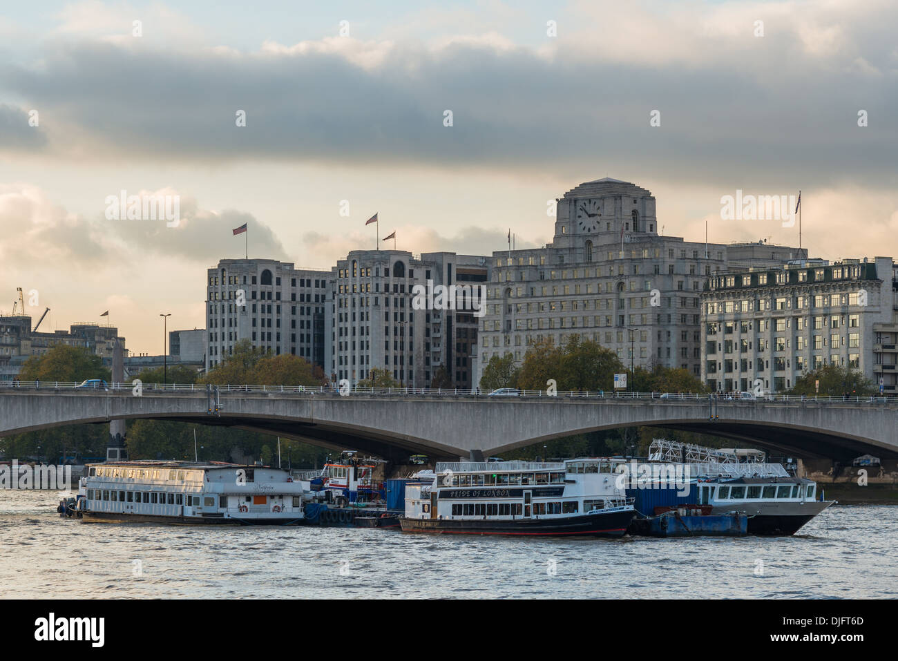 Thames pleasure cruises pass under Waterloo Bridge; landmark building Shell -Mex House forms the backdrop - Stock Image