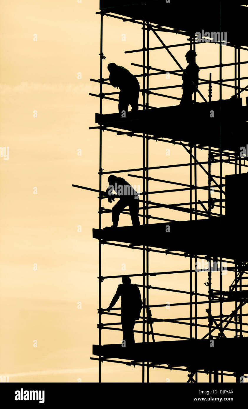 Scaffolders working on block of flats silhouetted againt bright Autumnal sky - Stock Image