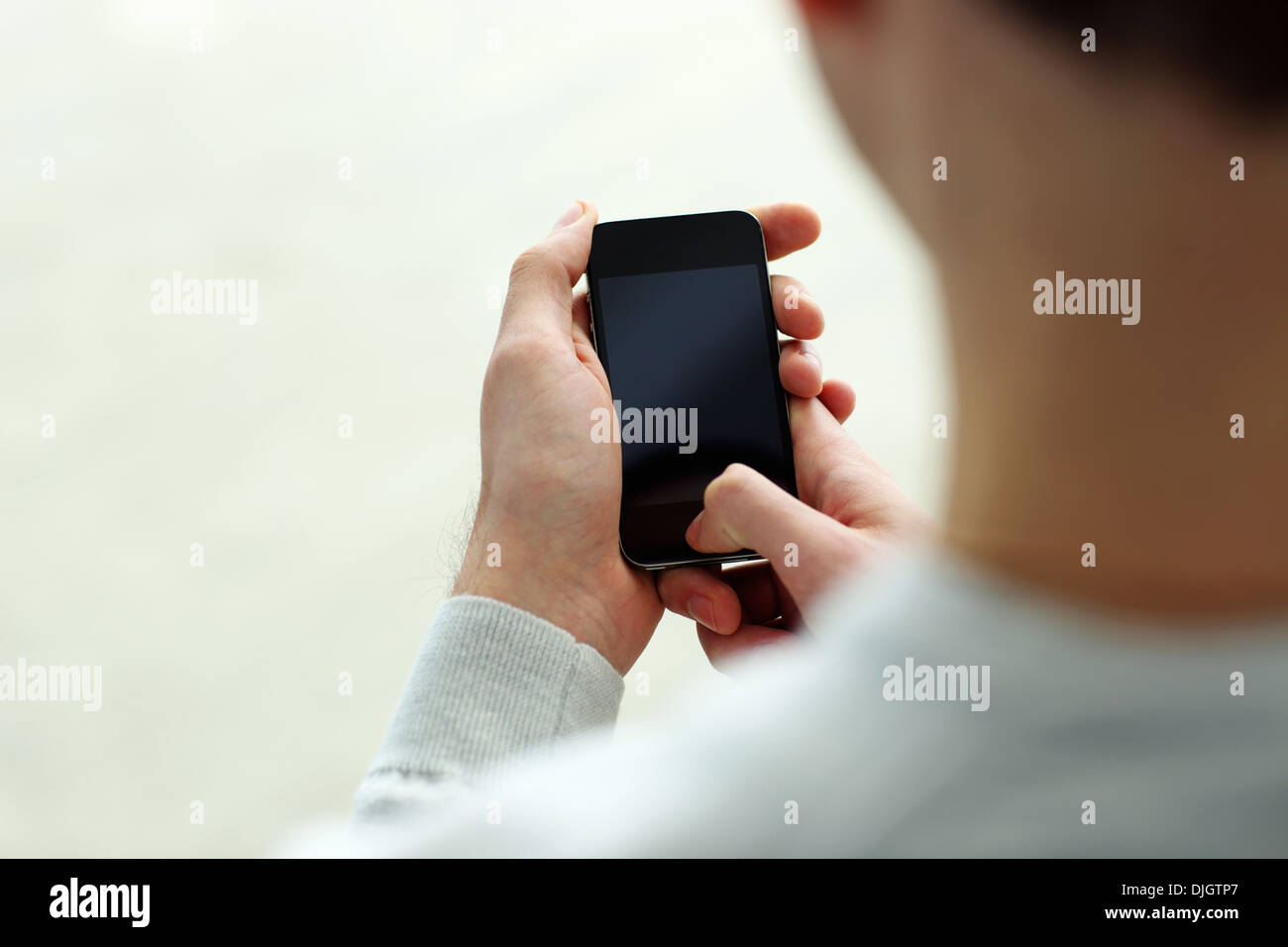 Closeup image of a man holding smartphone and looking at display isolated on a white background - Stock Image