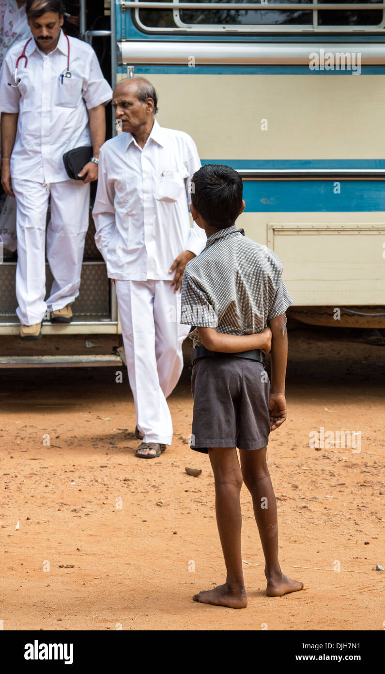 Indian boy looking at doctors getting off the bus at Sathya Sai Baba mobile outreach hospital service. Andhra Pradesh, India. - Stock Image
