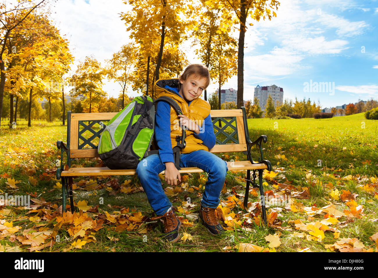86f91cf22e1d Happy 10 years old boy sitting on the bench with backpack after school with  backpack on