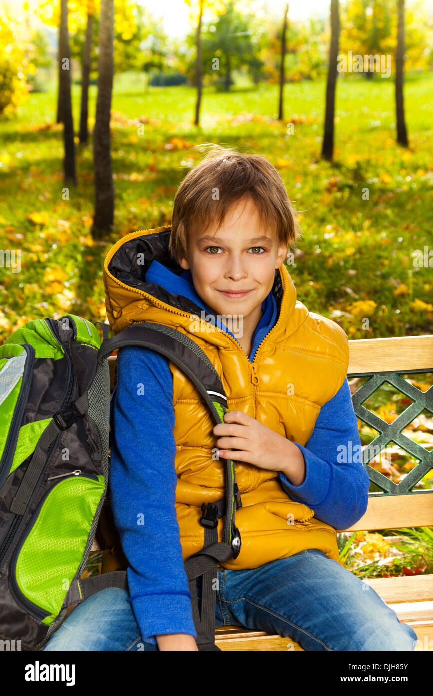 0f6934749f97 Portrait of happy 10 years old boy sitting on the bench with rucksack with backpack  after