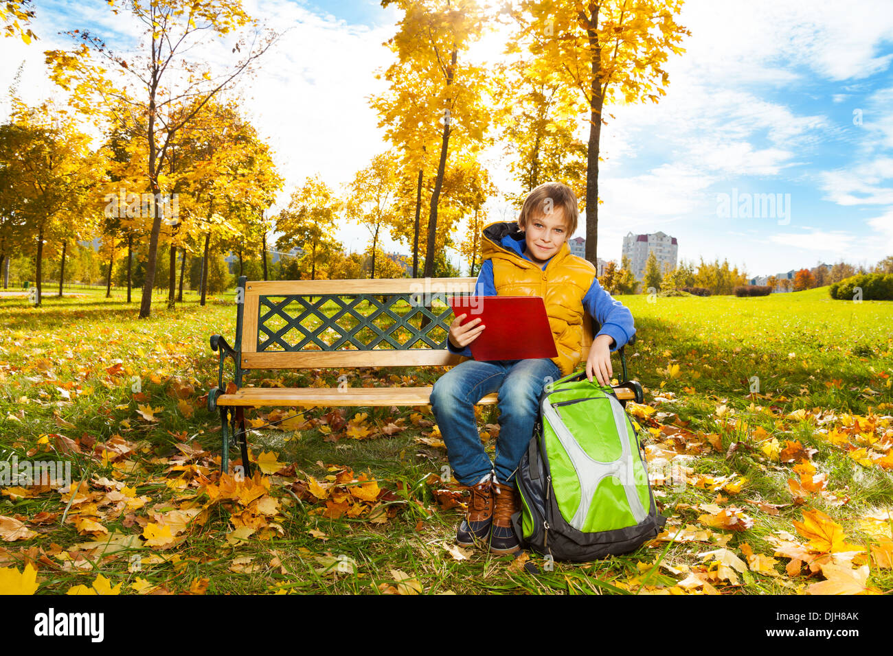 ac2dc8dbd7bd Happy 10 years old boy sitting on the bench with rucksack with backpack  after school with paper folder