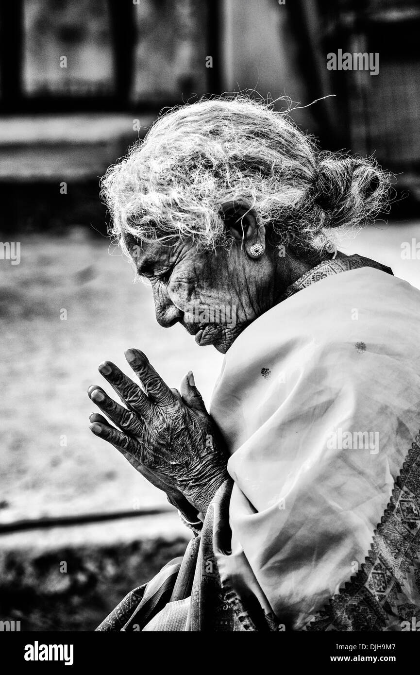 Old indian woman in prayer whilst waiting at sri sathya sai baba mobile outreach hospital