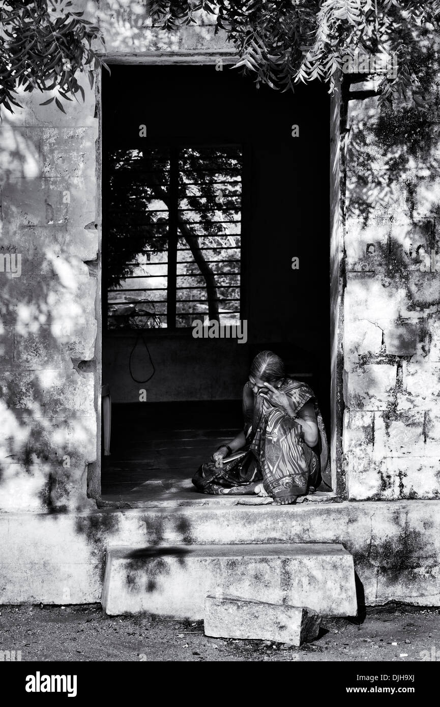Old Indian woman sat in a doorway at the Sri Sathya Sai Baba mobile outreach hospital clinic. Andhra Pradesh, India. Monochrome - Stock Image
