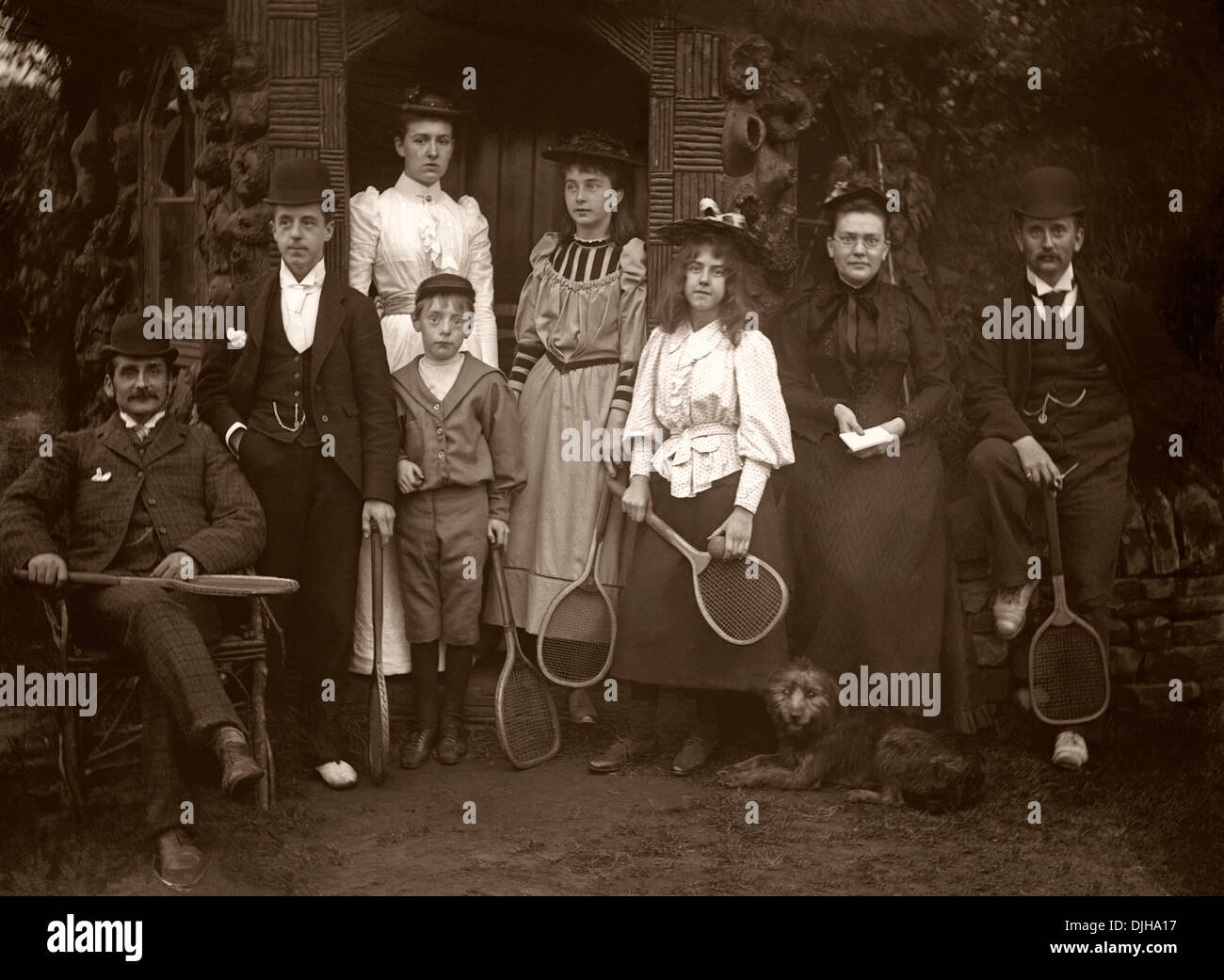A group of tennis players in the Victorian or Edwardian era c. 1900. They wear smart clothing for playing sport, including hats! - Stock Image