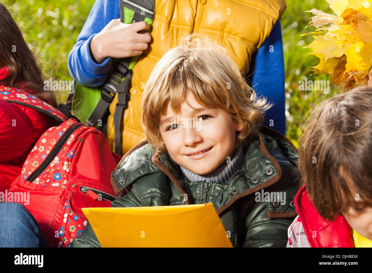 f6c183e5272e Portrait of beautiful blond boy sitting with friends holding paper folder -  Stock Image