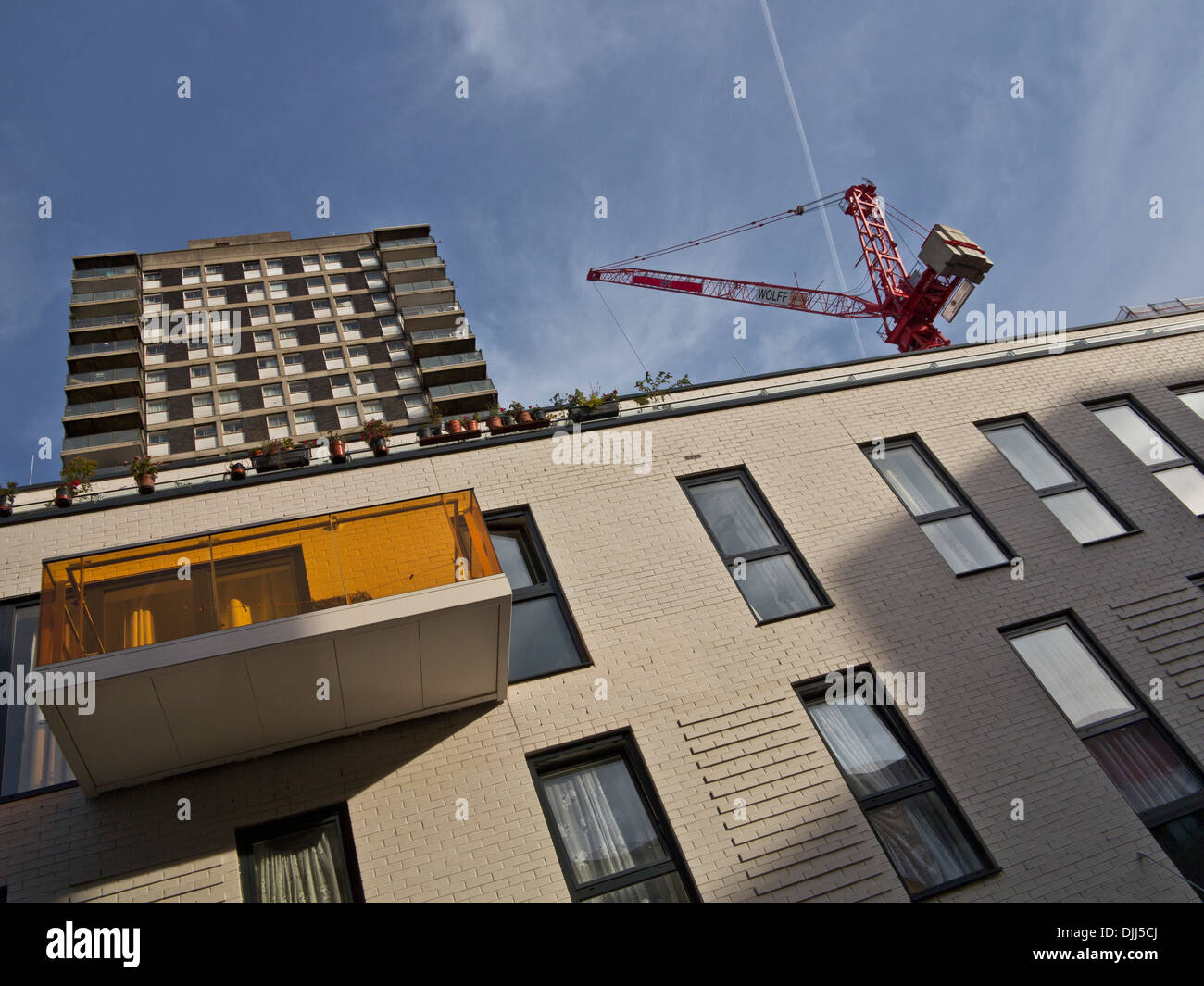 New construction work by old council housing near Aldsgate, London, UK - Stock Image