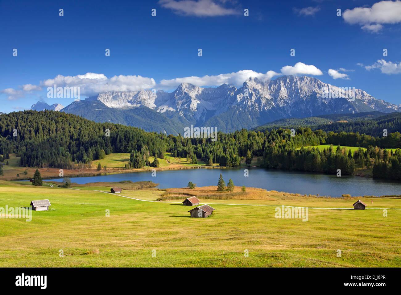 The Karwendel Mountain Range and huts along lake Gerold / Geroldsee near Mittenwald, Upper Bavaria, Germany - Stock Image