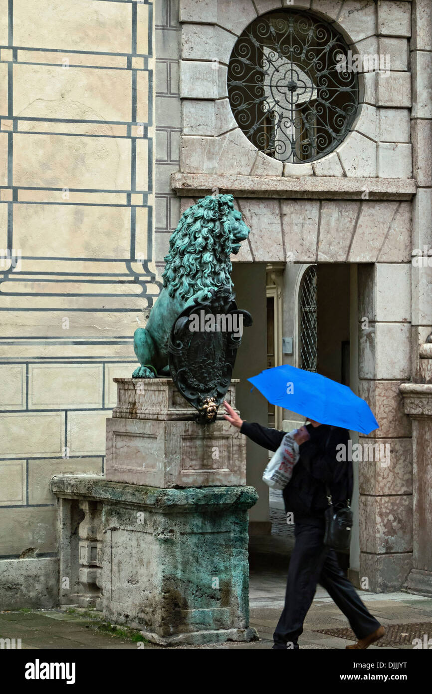 Man with a blue umbrella about to touch the Lion of the Royal Residence for Customary Good Luck, Munich Bavaria Germany - Stock Image
