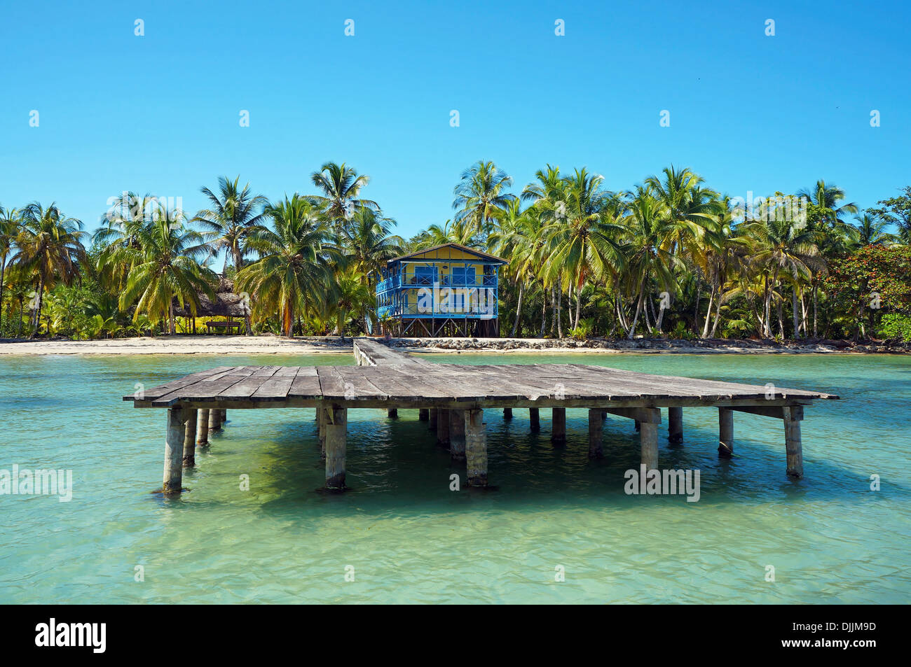 Tropical coastline with beach house and its dock, Caribbean sea - Stock Image