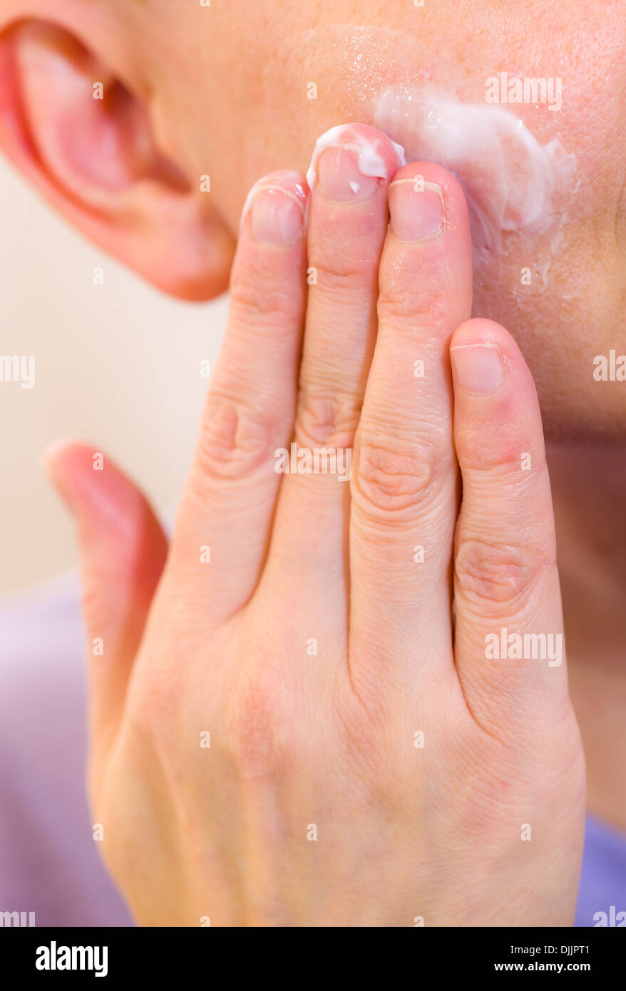 Mature woman spreading skincare cream on her cheek, vertical format - Stock Image