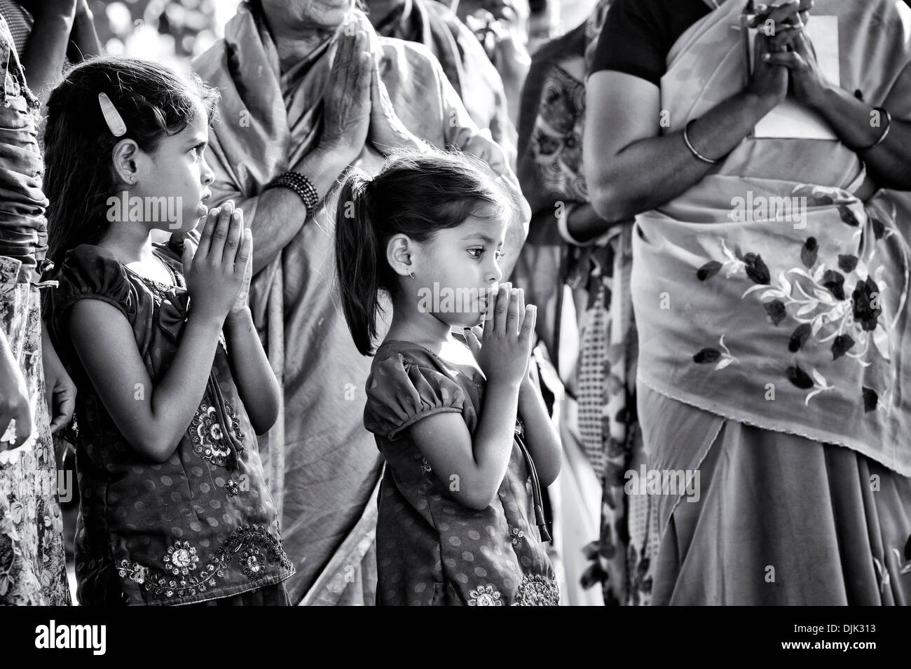 Rural Indian school girls sing devotional songs at Sri Sathya Sai Baba mobile outreach hospital service. Andhra Pradesh, India. - Stock Image