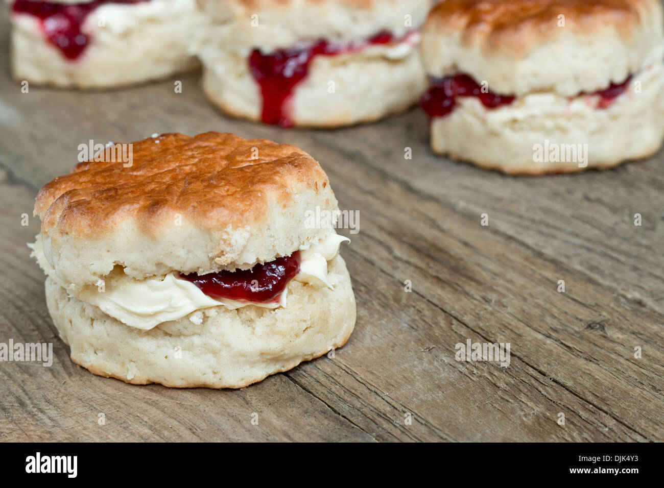 Cornish Cream Tea of scones filled with clotted cream and strawberry jam often served with hot beverages - Stock Image
