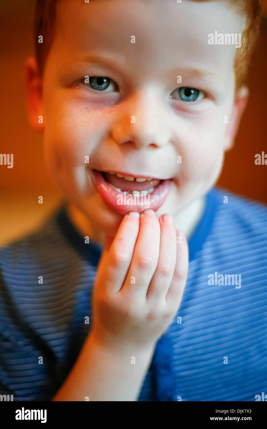 A boy showing his missing tooth - Stock Image