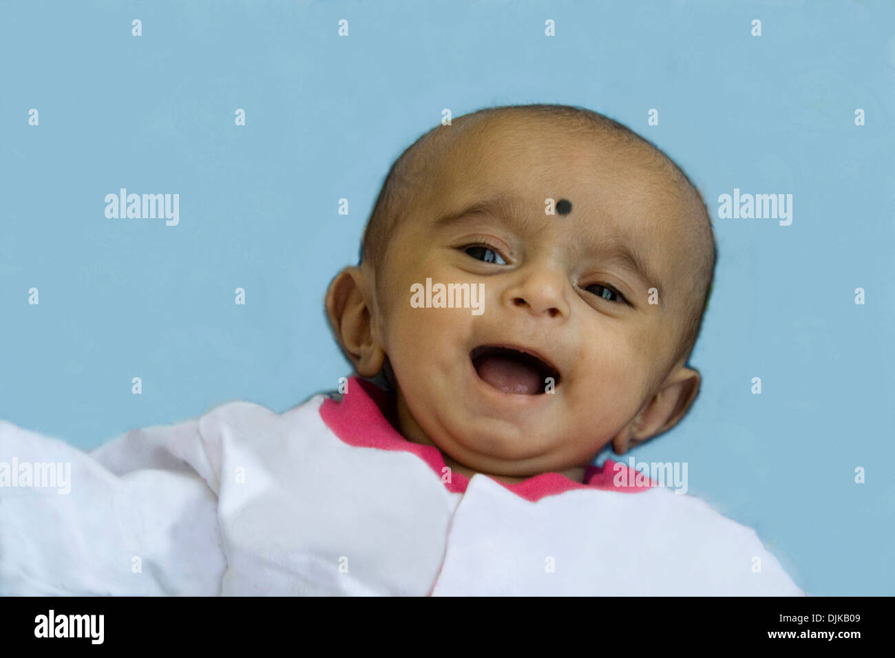 Charming giggle of young baby with mouth wide open - Stock Image