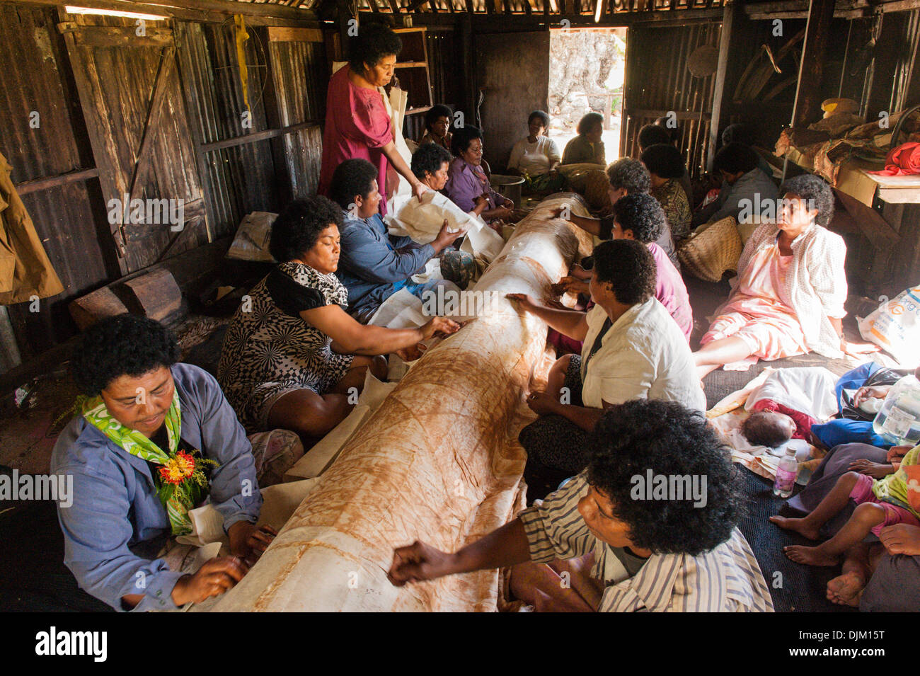 Large group of women working together stenciling on plain bark cloth to make a large traditional printed cloth called tapa. Fiji - Stock Image
