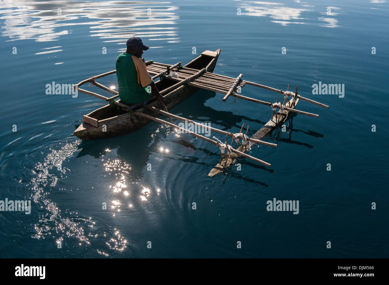 Frank, resident of Esema Bay, paddles pirogue, traditional dugout canoe with outrigger . Esema Bay, Efate, Vanuatu - Stock Image
