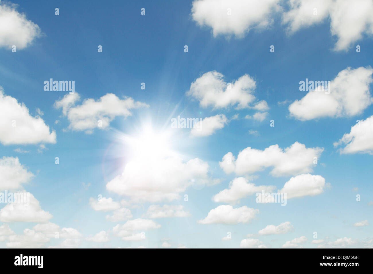 Bright sun in fluffy clouds sky - Stock Image