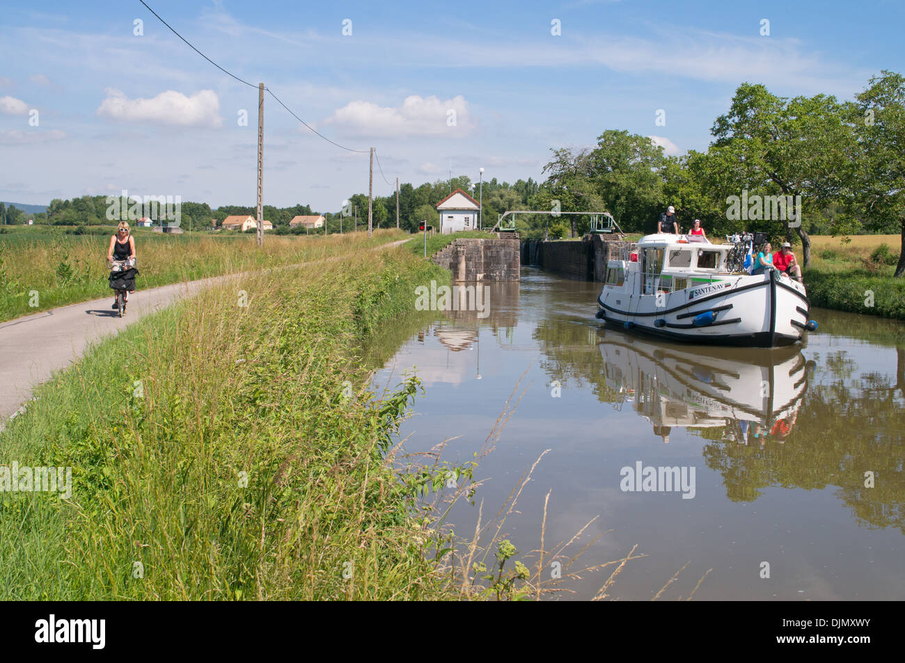 Female cyclist rides along towpath while pleasure craft sails along the Canal du Centre just beyond lock Burgundy eastern France - Stock Image