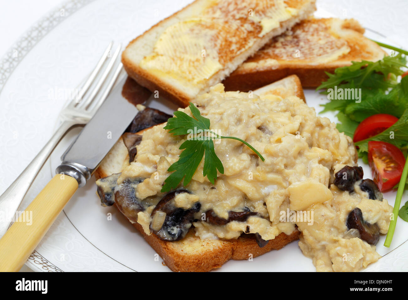 A breakfast or light lunch of scrambled eggs on toast made with fried mushrooms and shallots, Stock Photo