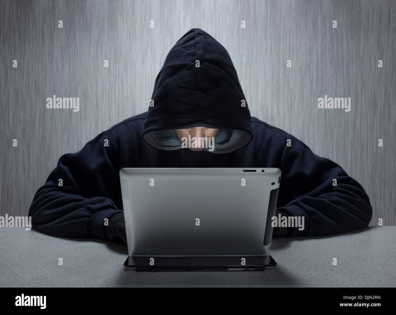 An anonymous hooded male using a tablet computer representing a cyber criminal. - Stock Image