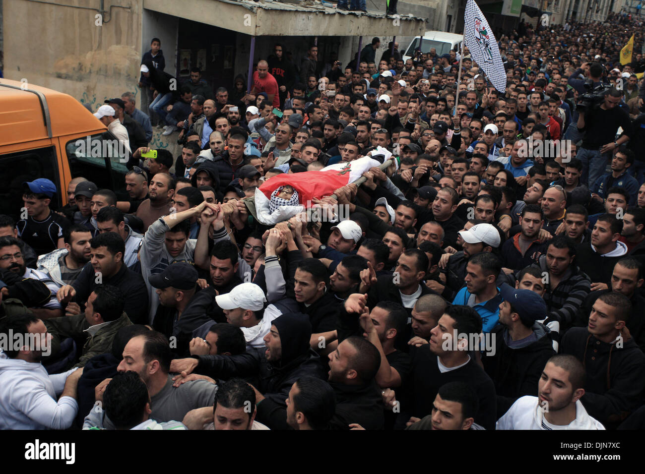 Qalandiya, West Bank, Palestinian Territory, . 29th Nov, 2013. Palestinian mourners carry the body of Mahmud Waji Awad, a Palestinian man who died the previous day of his injuries after he was shot in a 2012 clash with Israeli troops, during his funeral in the West Bank's Qalandiya camp on November 29, 2013 Credit:  Issam Rimawi/APA Images/ZUMAPRESS.com/Alamy Live News - Stock Image