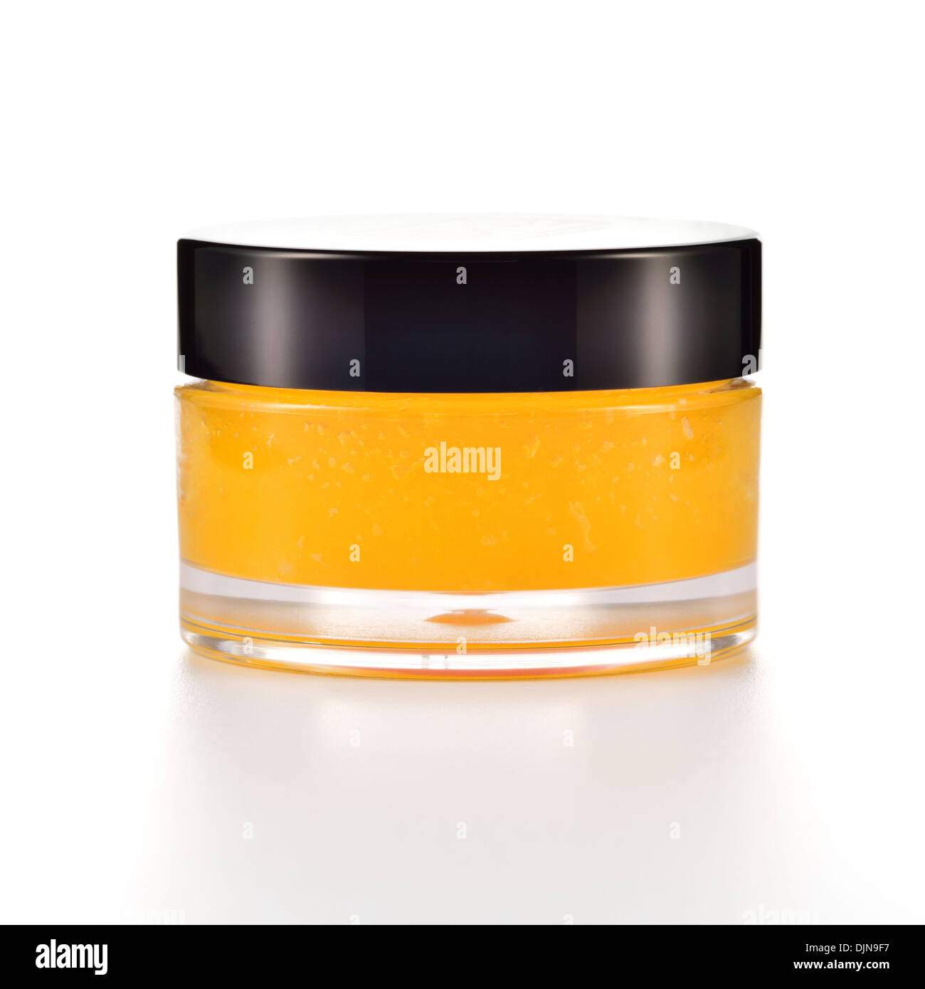 Orange sugar lip scrub on white background. Orange cosmetic in a glass jar. - Stock Image