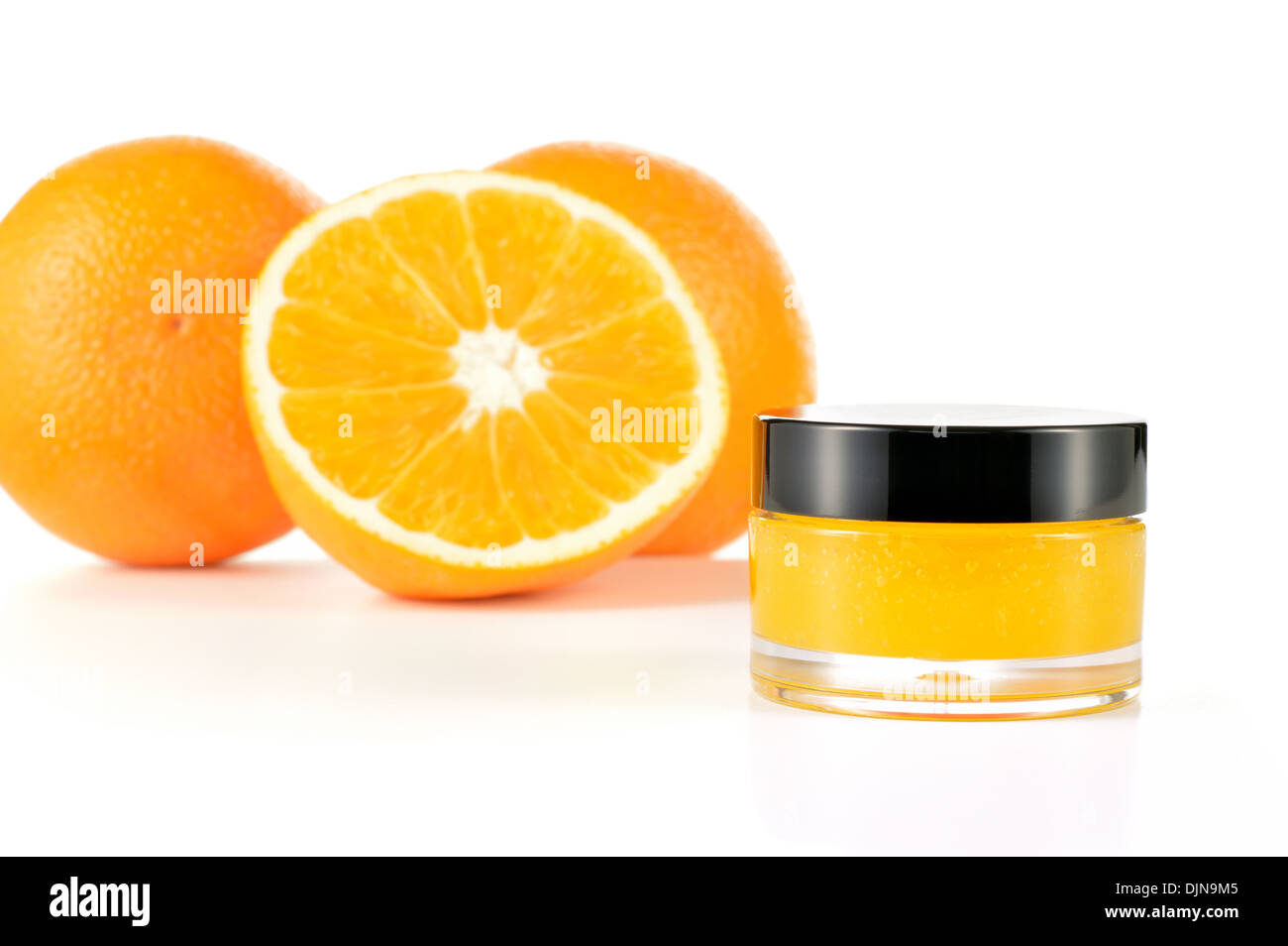Natural orange sugar lip scrub on white background. Orange cosmetic in a glass jar with oranges in a background. - Stock Image