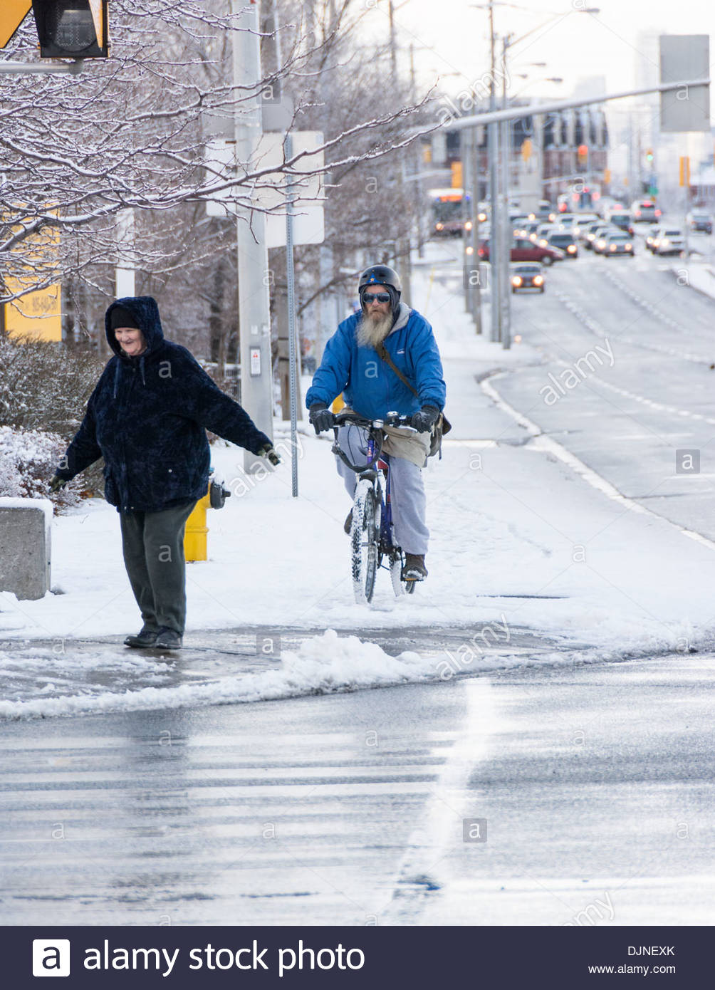 Normal people managing in the harsh Canadian winter. Snowfall in the city - Stock Image