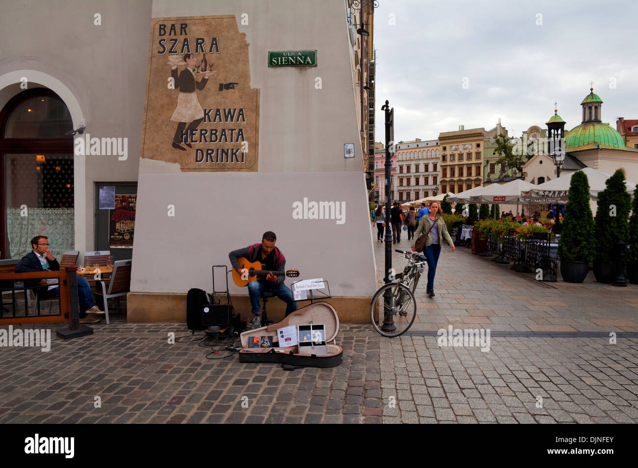 Street Busker playing guitar in Rynek Glowny The Main Market Square, Old Town, Krakow, Poland - Stock Image