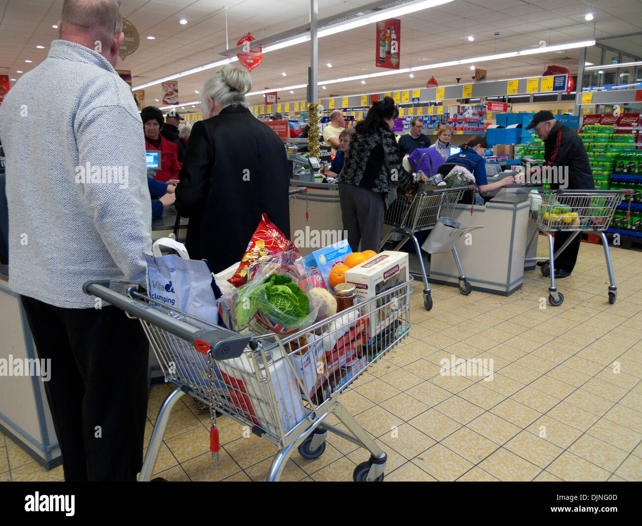 A customer with a full supermarket trolley cart in a queue to pay at the till  near the checkout counter in Aldi store Wales UK   KATHY DEWITT - Stock Image