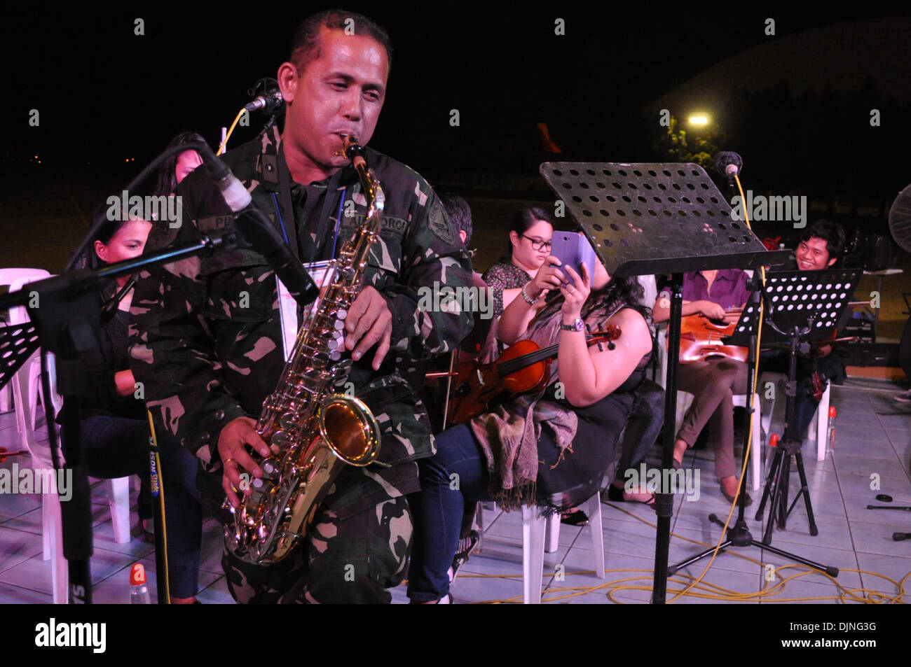 Pasay city, Manila, Philippines. 29th November 2013. A Philippine Airforce officer joins volunteer musicians in playing music inside the Villamor Airbase in Pasay city, south of Manila, Philippines on Friday, 29 November 2013. Credit:  George Calvelo/Alamy Live News - Stock Image