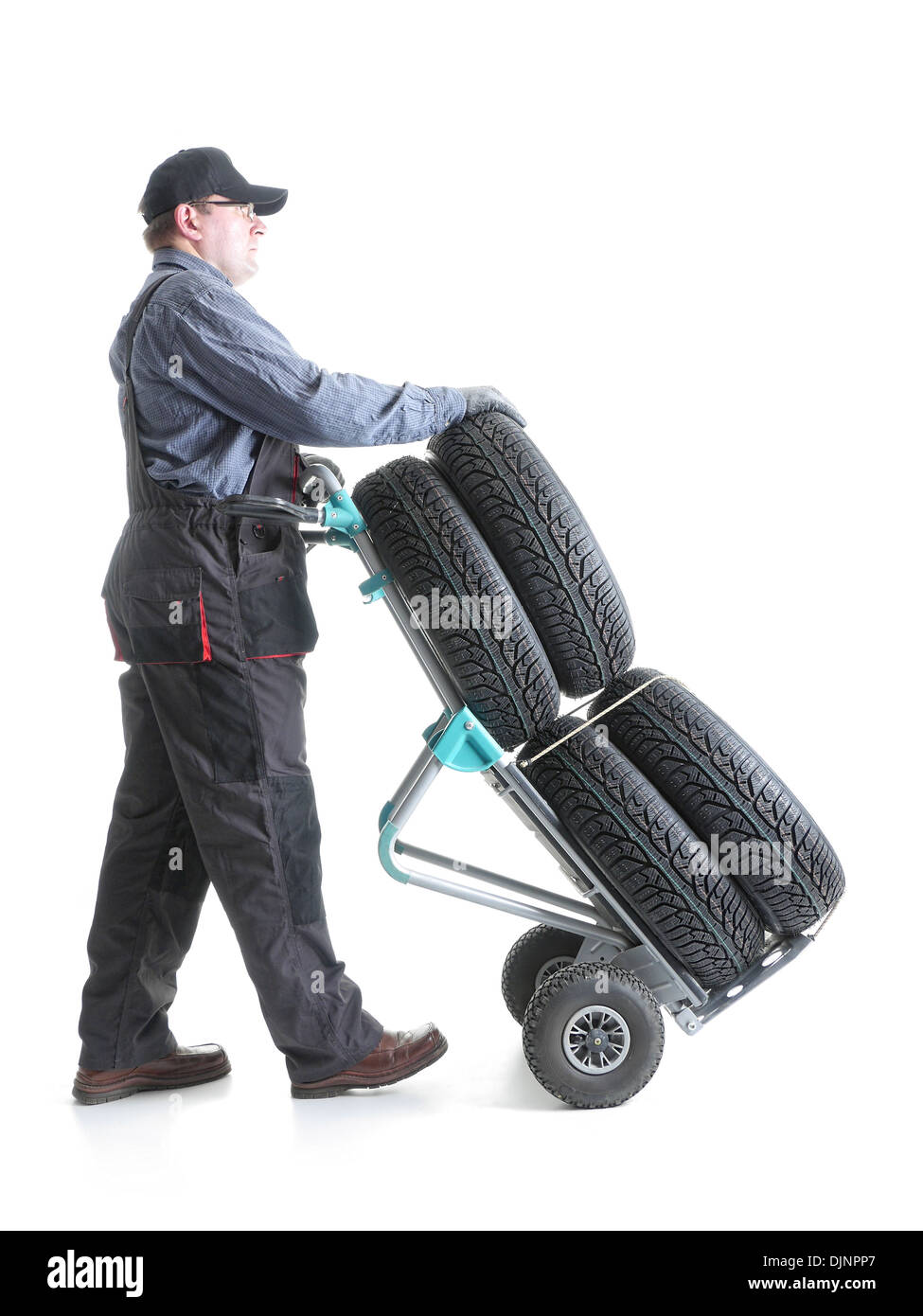 Serviceman carrying a set of four new car tires using hand truck shot on white - Stock Image