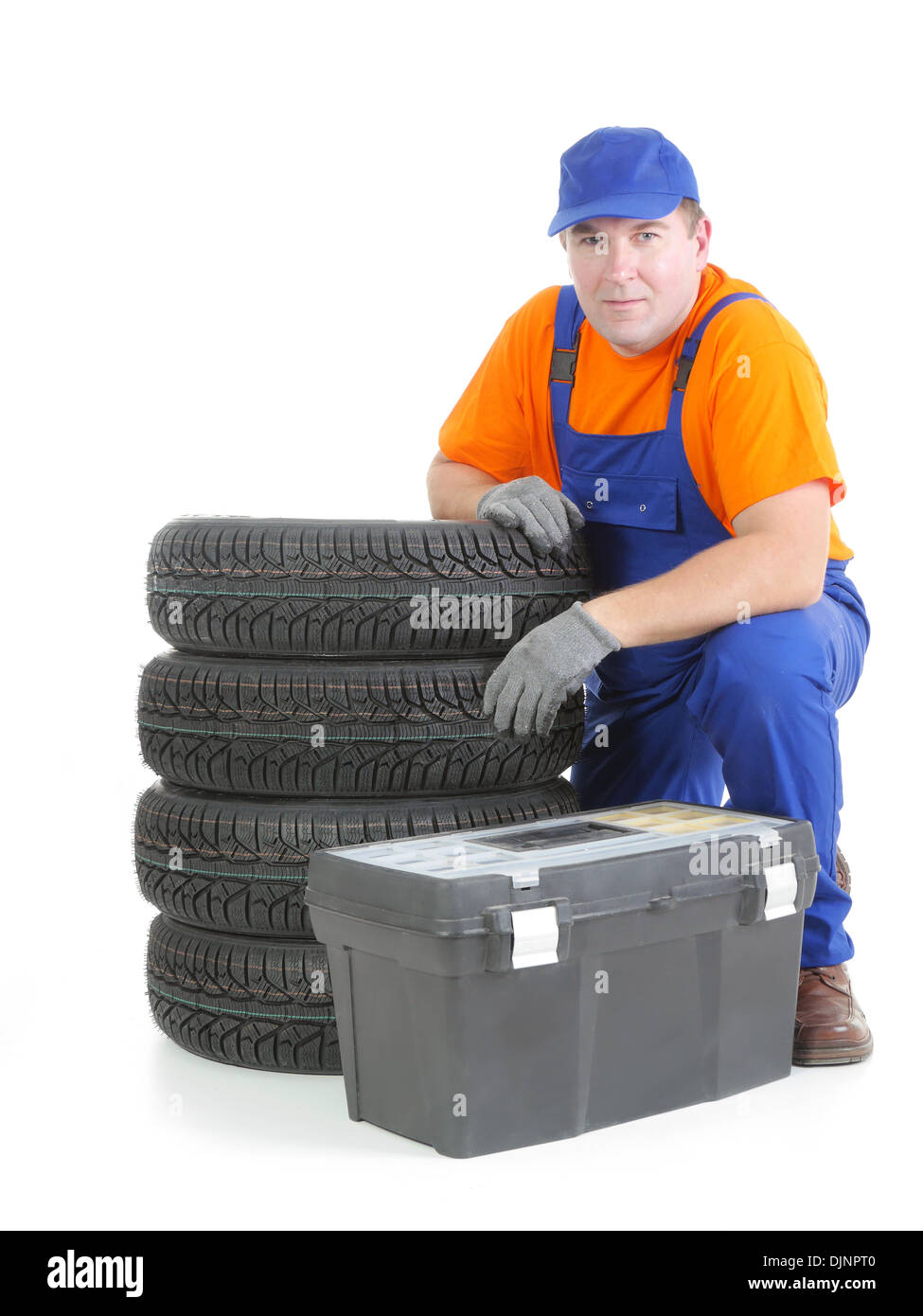 Mechanic wearing blue coveralls and orange t-shirt posing by pile of four new car tires and toolbox shot on white - Stock Image