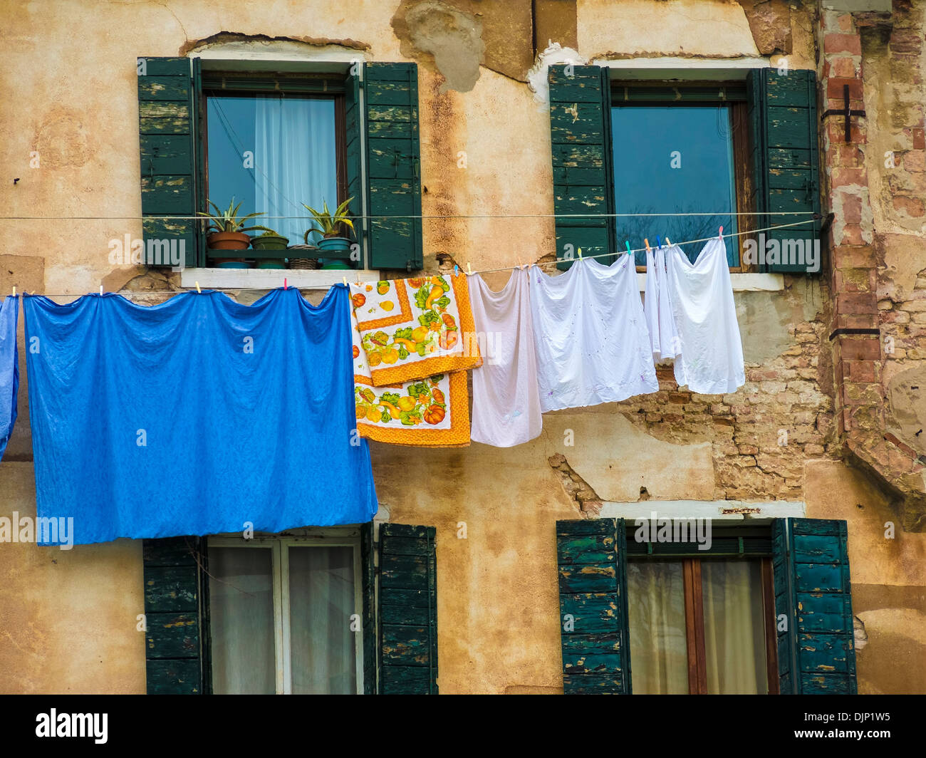 Brightly coloured laundry hanging on washing line between shuttered windows, Venice, Italy - Stock Image
