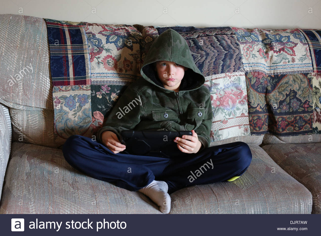 A young, sullen boy sitting on a sofa holding a tablet. - Stock Image