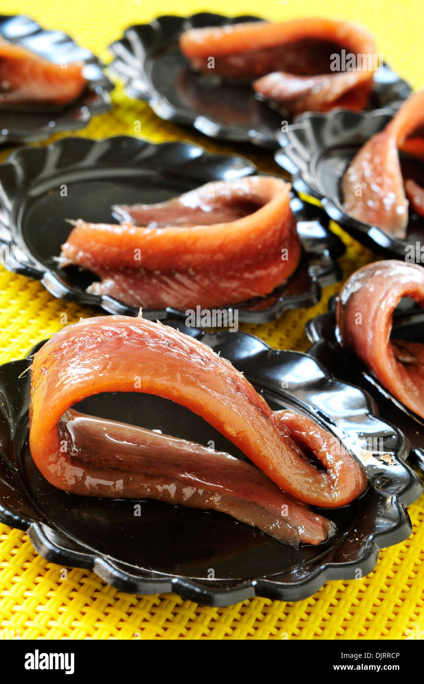 spanish anchovies served in small black plates as appetizer - Stock Image