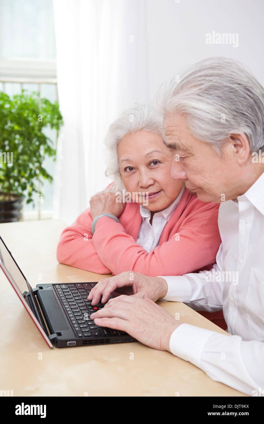 Senior couple using laptop - Stock Image