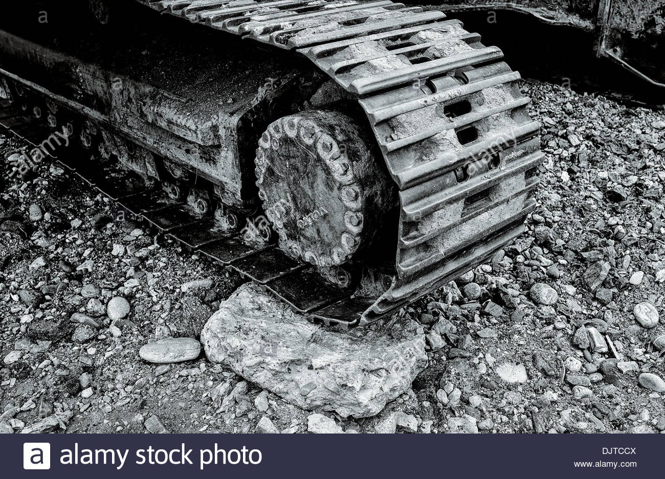 Detail of a excavator caterpillar track on land being cleared and graded for a new housing development block, South Korea - Stock Image