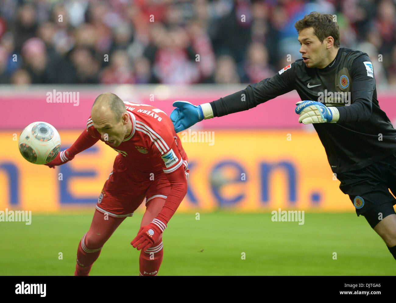 Munich, Germany. 30th Nov, 2013. Munich's Arjen Robben scores a 1-0 goal next to Braunschweig's Daniel Davari (R) during the German Bundesliga match between FC Bayern Munich and Eintracht Braunschweig at Allianz Arena in Munich, Germany, 30 November 2013. Photo: ANDREAS GEBERT (ATTENTION: Due to the accreditation guidelines, the DFL only permits the publication and utilisation of up to 15 pictures per match on the internet and in online media during the match.)/dpa/Alamy Live News - Stock Image