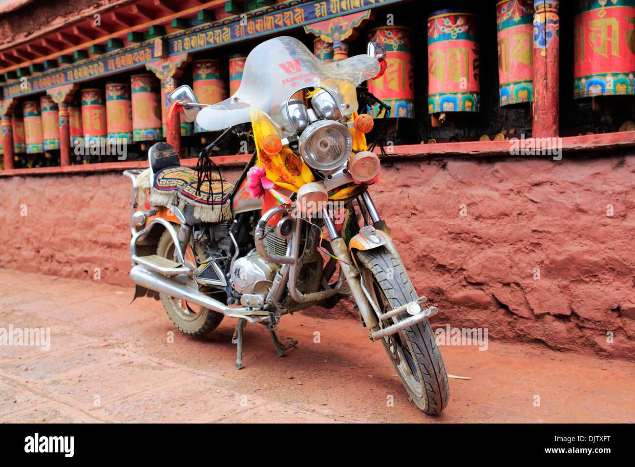 Motorbike and Prayer wheels, Sakya Monastery, Shigatse Prefecture, Tibet, China - Stock Image