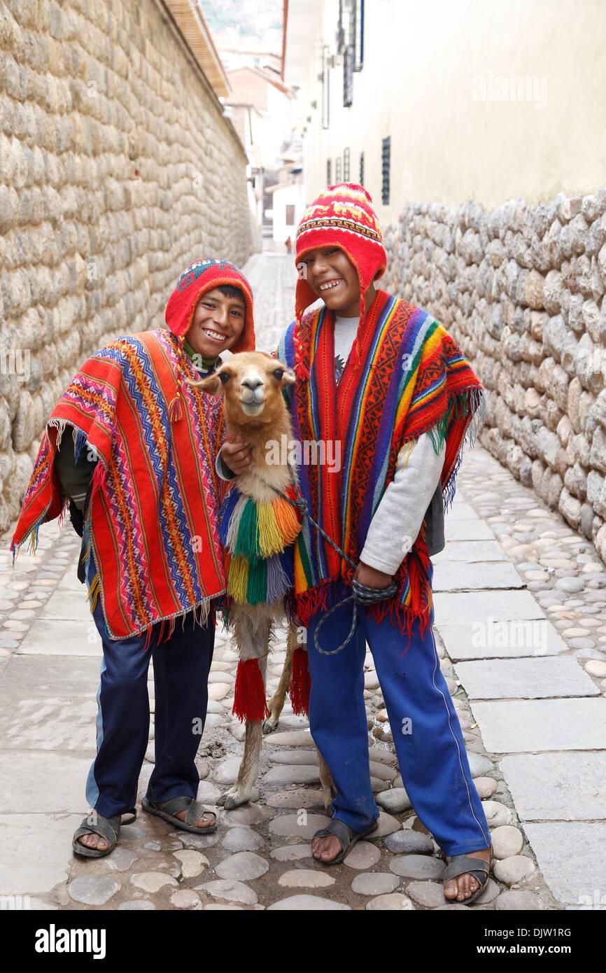 Quechua boys with a llama, Cuzco, Peru. - Stock Image