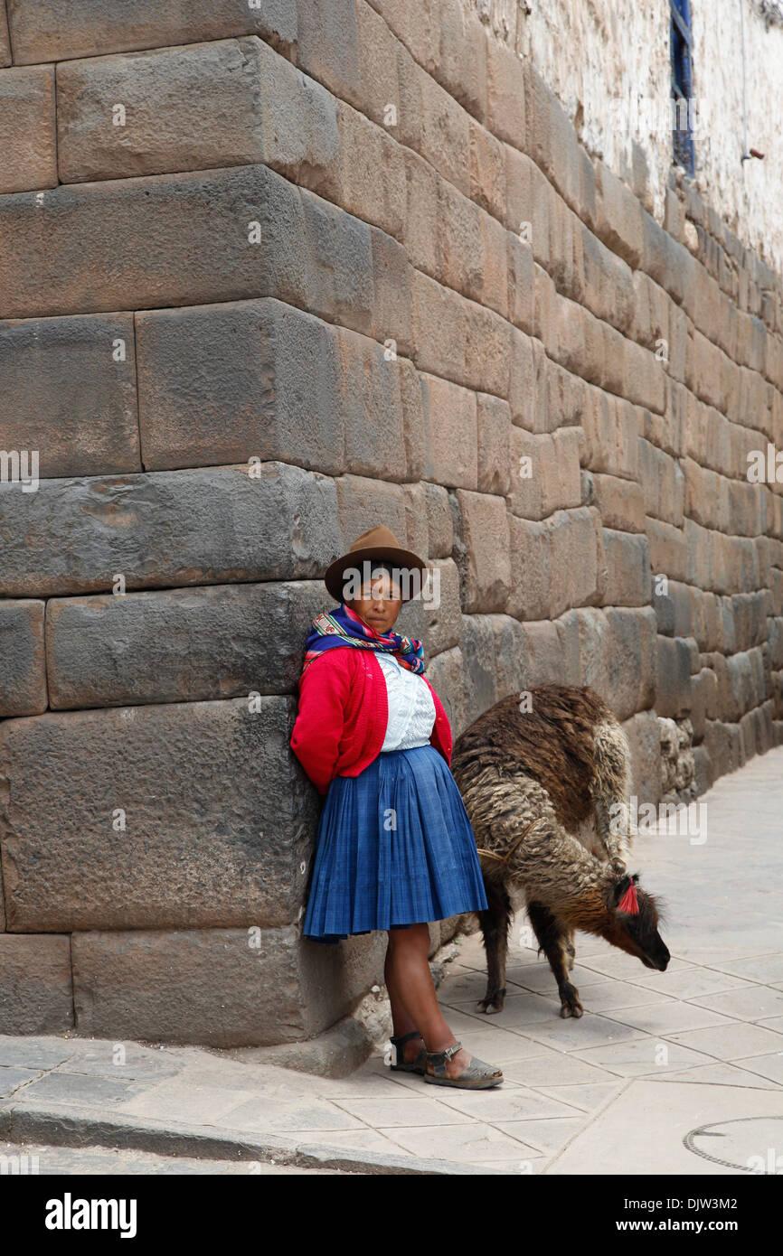 Quechua woman with llama along an inca wall in San Blas neighborhood, Cuzco, Peru. - Stock Image